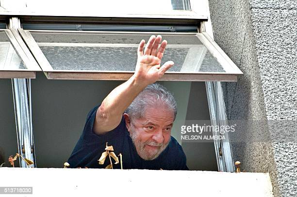 Former Brazilian President Luiz Inacio Lula da Silva waves at supporters from a window of the Workers Party state headquarters in Sao Paulo Brazil on...