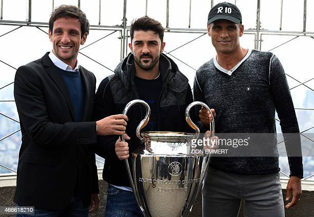 Former Brazilian right back Juliano Belletti Spanish striker David Villa and former Brazilian midfielder Rivaldo pose with the UEFA Champions League...