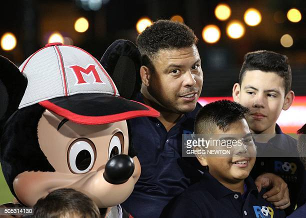 Former Brazilian World Cup star Ronaldo Nazario leans in to compare his ear with that of Mickey Mouse's during the kickoff at the start of the...
