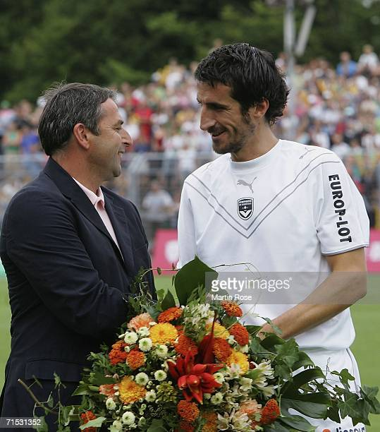 Former Bremen player Johan Micoud of Bordeaux is celebrated by Klaus Allofs manager of Bremen prior to the friendly match between Girondins Bordeaux...