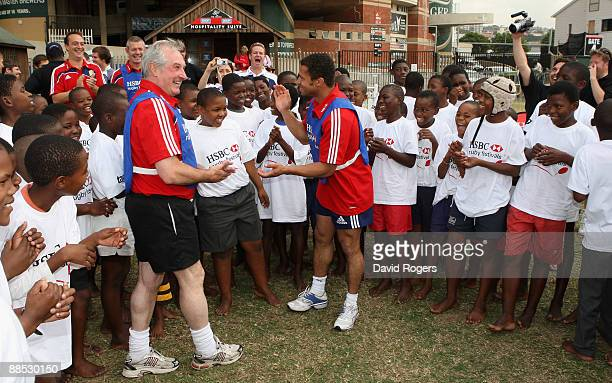 Former British and Irish Lions Gareth Edwards and Jason Robinson dance and sing with children as they sing Shosholoza during the HSBC Durban Rugby...