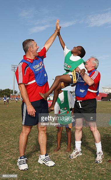 Former British and Irish Lions Gavin Hastings and Gareth Edwards give a child a high five during the HSBC Durban Rugby Coaching Festival at Kings...
