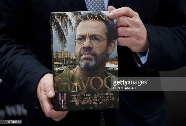 Former British Army officer Simon Mann poses for photographers with his new book entitled 'Havoc' during a book signing in central London on December...