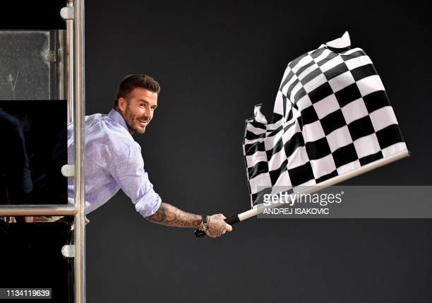 TOPSHOT Former British football player David Beckham waves the checkered flag as Mercedes' British driver Lewis Hamilton crosses the finish line...