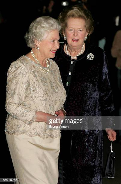 Former British Prime Minister Baroness Margaret Thatcher walks HM Queen Elizabeth II as they arrive for Thatcher's 80th birthday party at the...