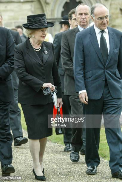 Former British Prime Minister Baroness Thatcher and former Conservative Party leader Michael Howard leave after attending the funeral of former...