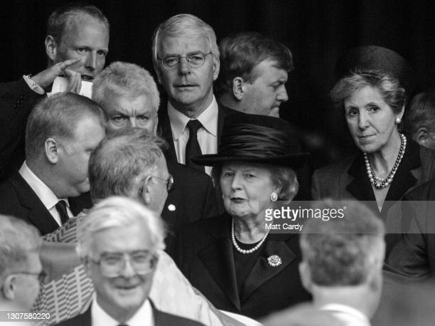 Former British Prime Minister Baroness Thatcher in hat and behind former Prime Minister John Major leave after attending the the funeral of former...