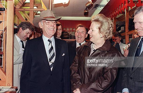 Former British Prime Minister Margaret Thatcher wearing the traditional Australian oilskin raincoat Drizabone smiles at her husband Denis wearing the...