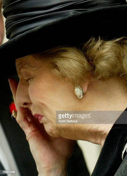 Former British Prime Minister Margaret Thatcher wipes tears from her eyes as she leaves the memorial service for her husband Denis October 30 2003 in...