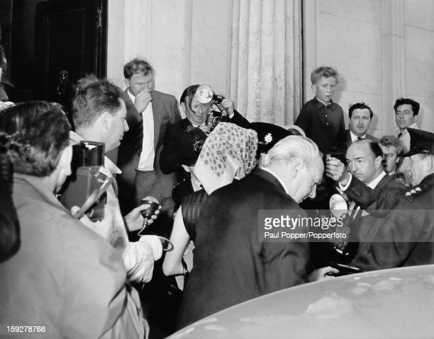 Former British Secretary of State for War John Profumo and his wife Valerie Hobson are surrounded by photographers as they arrive at their home...