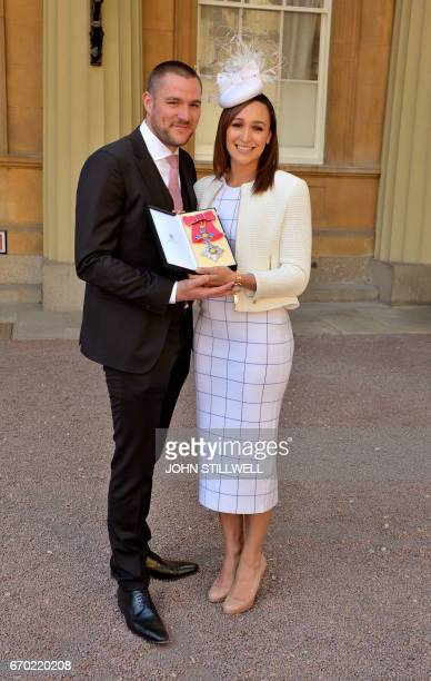 Former British track and field athlete Jessica EnnisHill accompanied by her husband Andy holds her award after she was made a Dame Commander of the...