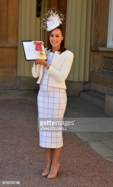 Former British track and field athlete Jessica EnnisHill holds her award after she was made a Dame Commander of the Order of the British Empire for...