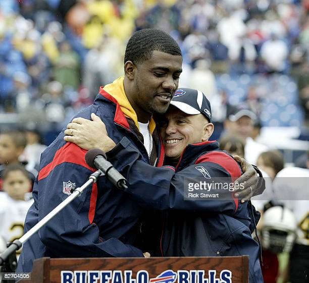 Former Buffalo Bills player Kevin Everett hugs Buffalo Bills surgeon Andrew Cappucino after Everett received the George Halas award during halftime...