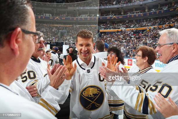 Former Buffalo Sabres captain Jason Pominville is greeted by season ticket holders during a pregame ceremony honoring the team's 50th anniversary...
