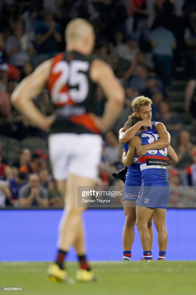Former Bulldogs player Jake Stringer of the Bombers looks on as Mitch Wallis and Caleb Daniel of the Bulldogs celebrate their win on the final siren after the round three AFL match between the Western Bulldogs and the Essendon Bombers at Etihad Stadium on April 8, 2018 in Melbourne, Australia.