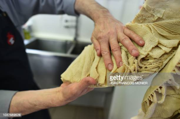 Former butcher Laurent Legoff holds the lining of a cow's stomach used to prepare skewered tripes in the laboratory of The house of the tripe on...