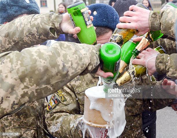 Former cadets of the military faculty of National Technical University pour champagne on February 28 2015 during a graduation ceremony in...
