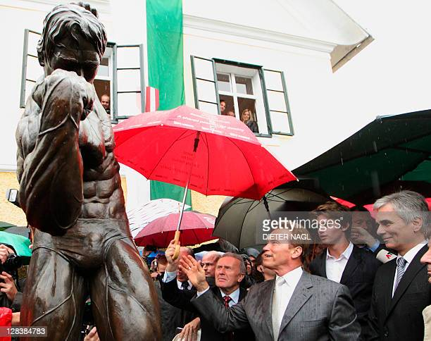 Former California Governor Arnold Schwarzenegger and and Austrian Chancellor Werner Faymann attend on October 7 2011 the unveiling of a statue during...