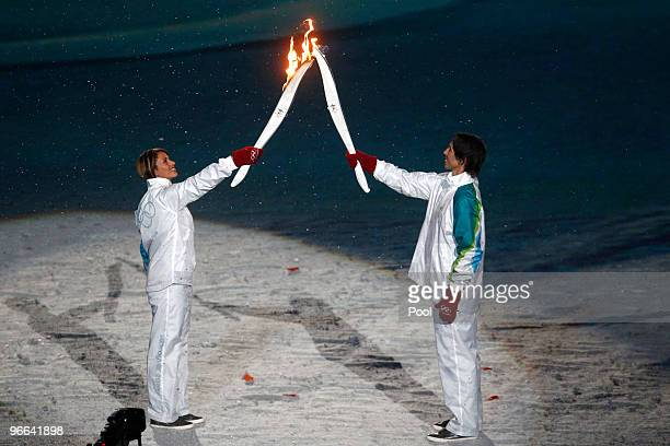 Former Canadian speed skater Catriona LeMay Doan passes the Olympic flame to NBA basketball player Steve Nash of the Phoenix Suns during the Opening...