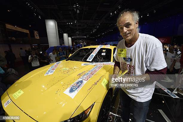 Former candidate of the New Anticapitalist Party to the 2012 French presidential election unionist Philippe Poutou puts stikers on a Ford Mustang...