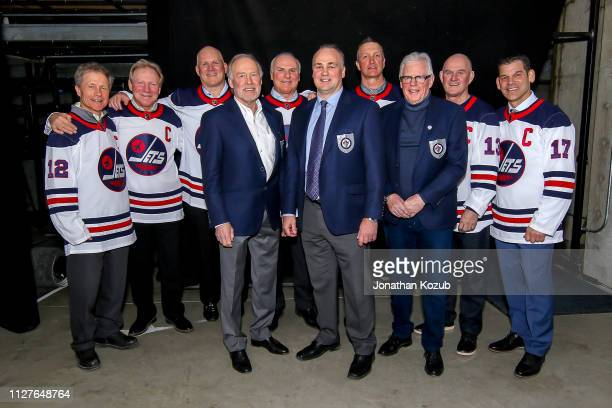 Former Captains and Hall of Fame Members of the Winnipeg Jets pose together following the pregame ceremony for NHL action between the Jets and the...