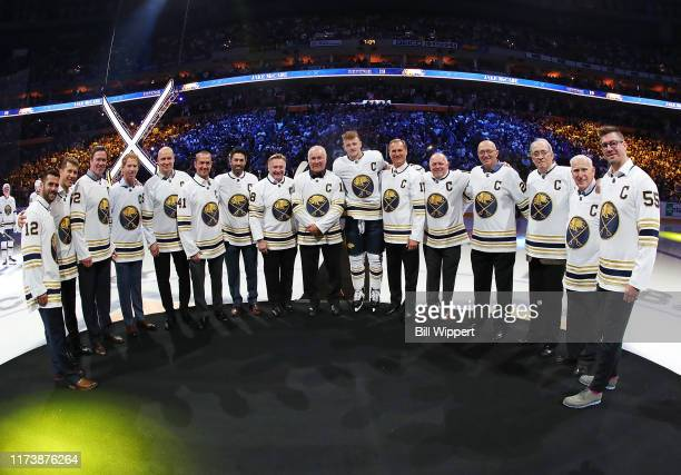 Former captains of the Buffalo Sabres pose with current captain Jack Eichel prior to an NHL game against the New Jersey Devils on October 5, 2019 at...