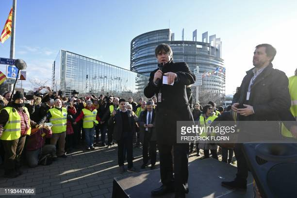 Former Catalan regional president and new MEP's Carles Puigdemont , past his former health minister and new MEP's Antoni Comin , delivers a speech as...