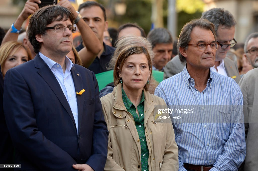 ?(FromR) Former Catalan regional president Artur Mas, president of the Catalan parliament Carme Forcadell and Catalan regional president Carles Puigdemont attend a demonstration on October 21, 2017 in Barcelona, to support two leaders of Catalan separatist groups, Jordi Sanchez and Jordi Cuixart, who have been detained pending an investigation into sedition charges. Spain announced that it will move to dismiss Catalonia's separatist government and call fresh elections in the semi-autonomous region in a bid to stop its leaders from declaring independence. / AFP PHOTO / Josep LAGO