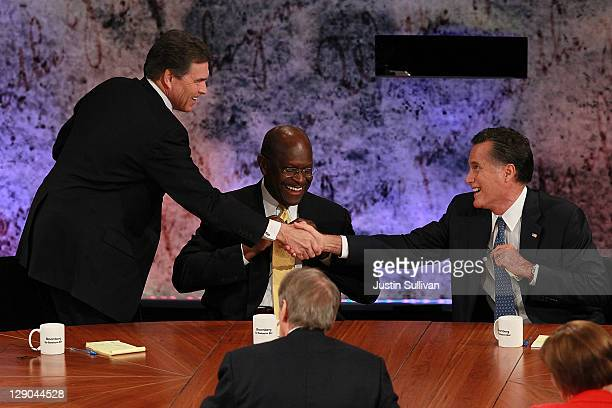 Former CEO of Godfather's Pizza Herman Cain looks on as Texas Gov Rick Perry and Former Massachusetts Gov Mitt Romney shake hands at the conclusion...