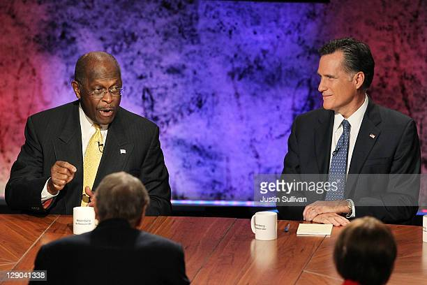 Former CEO of Godfather's Pizza Herman Cain speaks as former Massachusetts Gov Mitt Romney looks on during the Republican Presidential debate hosted...