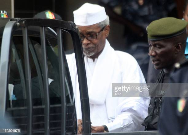 Former Chadian dictator Hissene Habre is escorted by military officers after being heard by judge on July 2, 2013 in Dakar. Senegalese authorities...