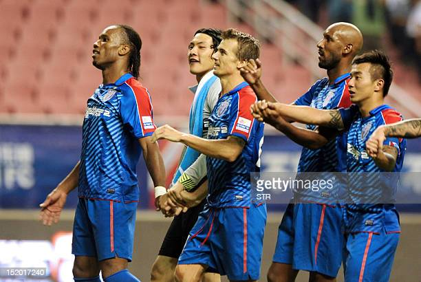 Former Chelsea star Didier Drogba and teammate Nicolas Anelka with their Shanghai Shenhua teammates walk off the pitch after beating Liaoning Whowin...