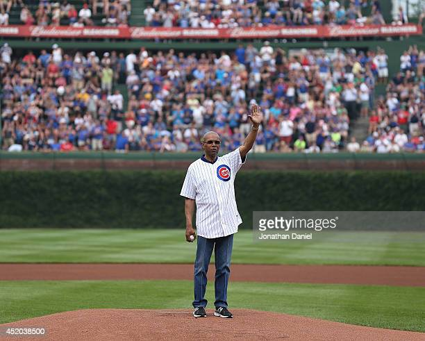 Former Chicago Bear and Hall of Fame player Gayle Sayers waves to the crowd before throwing a ceremonial first pitch before the Chicago Cubs take on...