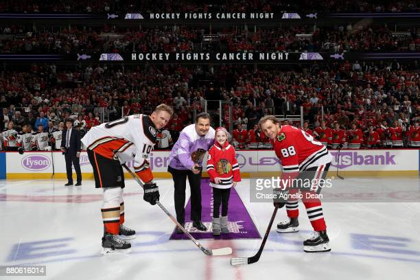 Former Chicago Blackhawk Eddie Olczyk and 9yearold cancer patient Lauren Graver drop the puck with Corey Perry of the Anaheim Ducks and Patrick Kane...