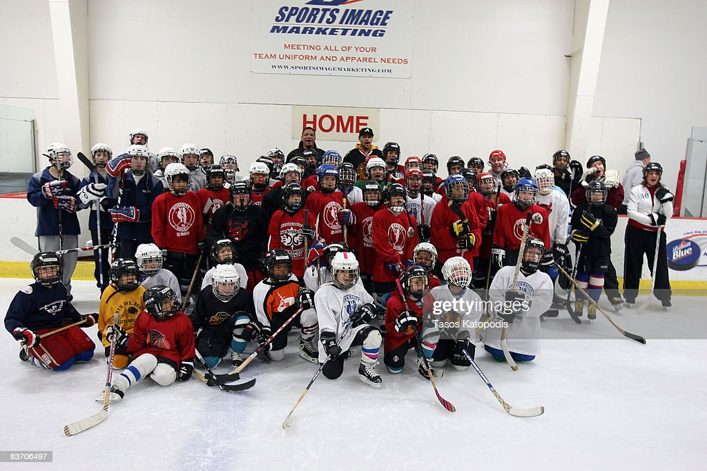 Former Chicago Blackhawk Tony McKegney and Chicago Blackhawk's Dustin Byfuglien pose in group photo with players at the AHAI Team Clinic November 15, 2008 in Glen Ellyn, Illinois.