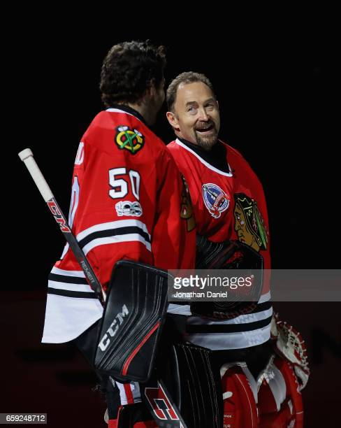 Former Chicago Blackhawks goaltender Ed Belfour greets Corey Crawford as he is honored before a game against the Dallas Stars at the United Center on...