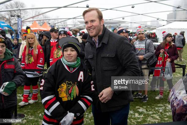 Former Chicago Blackhawks player Bryan Bickell poses for a photo with a fan during the Bridgestone NHL Winter Classic Park fan festival at Millenium...