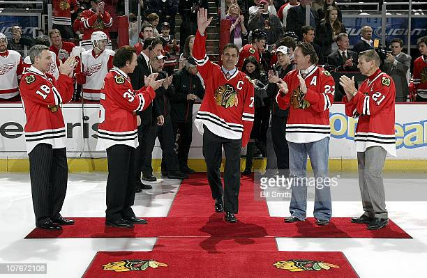 Former Chicago Blackhawks player Chris Chelios walks out to be honored on 'Chris Chelios Night' with NHL Hall of Famers' Denis Savard Tony Esposito...