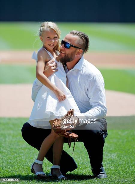 Former Chicago White Sox pitcher Mark Buehrle hugs his daughter Brooklyn after she threw out a ceremonial first pitch before the game between the...