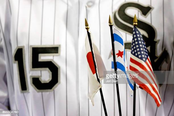 Former Chicago White Sox player Tadahito Iguchi holds miniture flags while he is honored by Naoki Ito consul general of Japan in Chicago before the...