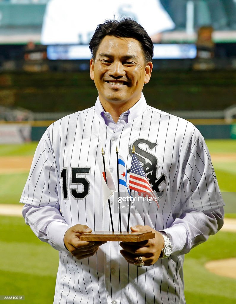Former Chicago White Sox player Tadahito Iguchi holds miniture flags and smiles while he is honored by Naoki Ito (not pictured), consul general of Japan in Chicago, before the game between the Chicago White Sox and the Los Angeles Angels of Anaheim at Guaranteed Rate Field on September 28, 2017 in Chicago, Illinois.