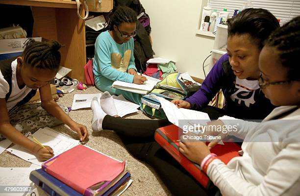 Former Chicagoans and sisters from left Khamani Reynold Mariah Davis 15 and Makalah Davis far right gather in their room after school and do homework...