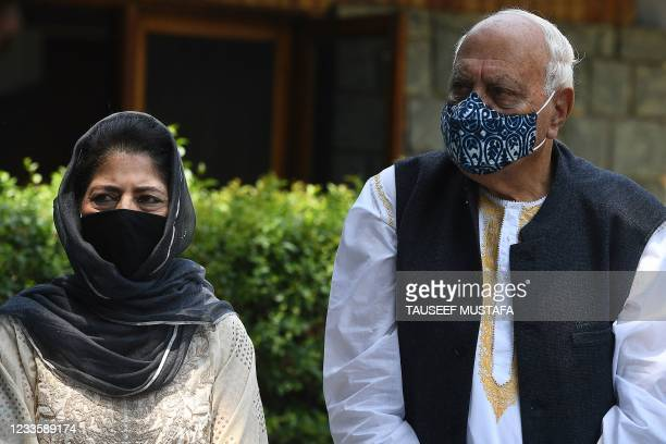 Former chief minister of Jammu and Kashmir Mehbooba Mufty stands next to former chief minister Farooq Abdullah during a press conference after a...