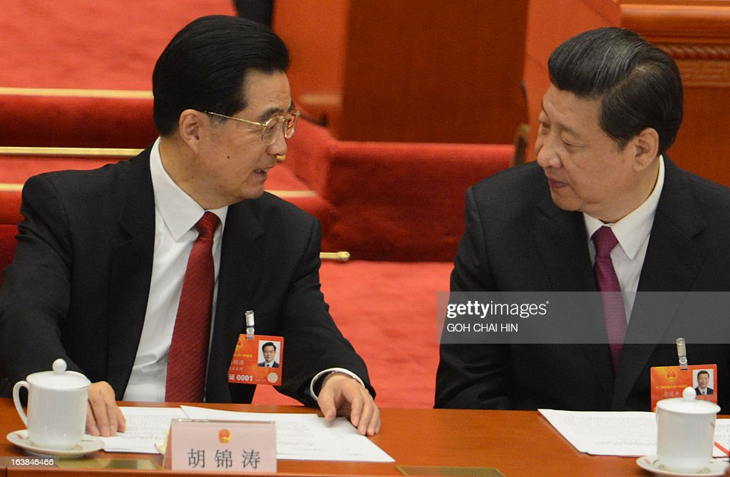 Former Chinese president Hu Jintao (L) talks to newly-elected President Xi Jinping at the closing session of the National People's Congress (NPC) at the Great Hall of the People in Beijing on March 17, 2013. Xi said he would fight for a 'great renaissance of the Chinese nation', in his first speech as head of state of the world's most populous country.