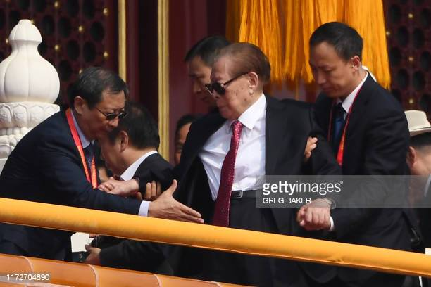 Former Chinese president Jiang Zemin is assisted as he leaves after a military parade in Tiananmen Square in Beijing on October 1 to mark the 70th...