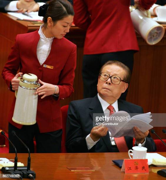Former Chinese President Jiang Zemin looks up at a hostess after she refills his cup 15 October 2007 at the Great Hall of the People in Beijing while...