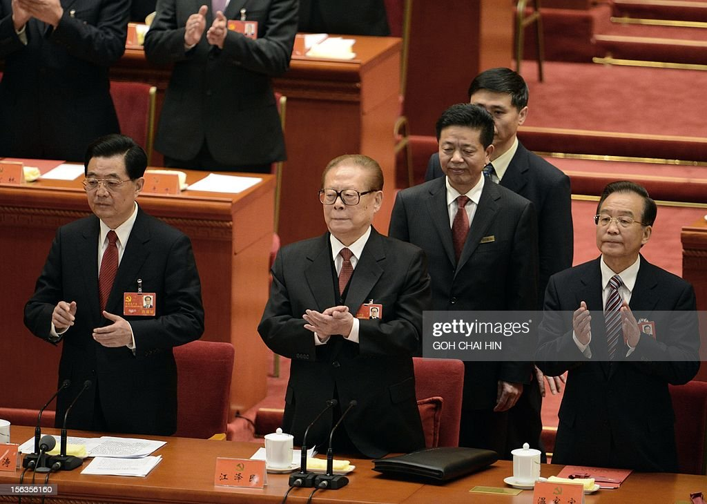 Former Chinese president Jiang Zemin (C) together with President Hu Jintao (L) with Premier Wen Jiabao (R) clap hands during the closing of the 18th Communist Party Congress at the Great Hall of the People in Beijing on 14 November 2012. The week-long Communist Party Congress will end with a transition of power to Chinese Vice President Xi Jinping, who will govern for the coming decade amid growing pressure for reform of the communist regime's iron-clad grip on power.