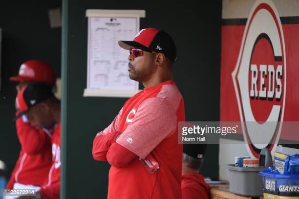 Former Cincinnati Reds player Barry Larkin looks on from the Reds dugout prior to a spring training game against the Chicago Cubs at Goodyear...