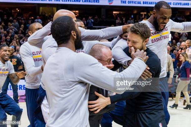 Former Cleveland Cavalier Matthew Dellavedova of the Milwaukee Bucks is mobed by his former teammates as Cavs general manager David Griffin presents...