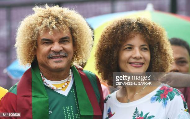 Former Colombian footballer Carlos Valderrama who played in three World Cup tournaments poses for pictures with his wife Elvira while holding a...